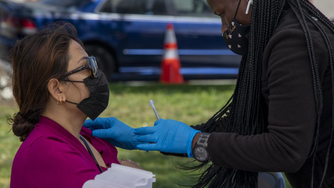 A woman receives a COVID-19 vaccine during a mobile vaccine clinic at the rear of MacArthur Park in Central Long Beach