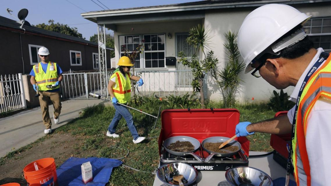 Bharat Dungrani, an environmental health specialist for the L.A. County Health Dept, removes moisture from soil samples collecte