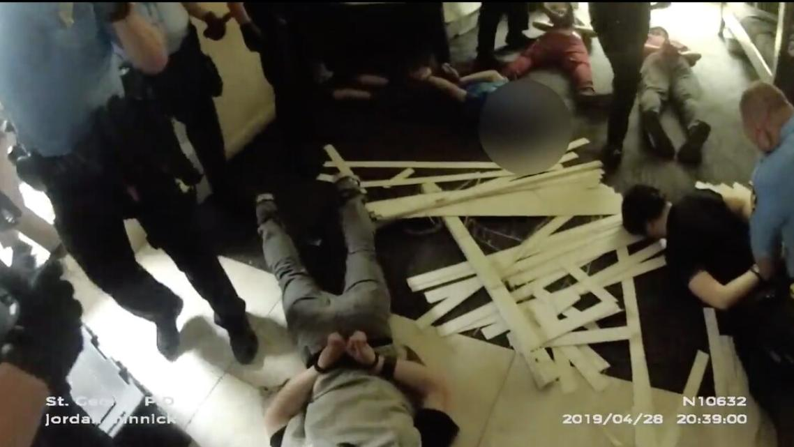 This screenshot of body camera footage shows police handcuffing teenage boys during a riot at Red Rock Canyon School on April 28