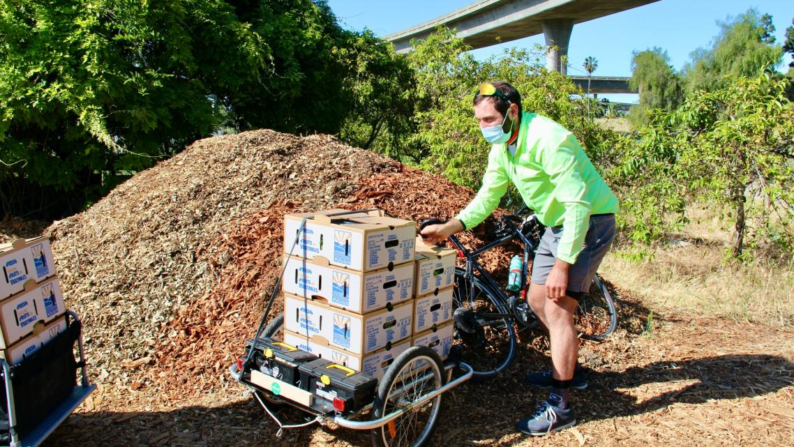 Volunteers with the Silicon Valley Bicycle Coalition load boxes of food onto their bicycles for delivery