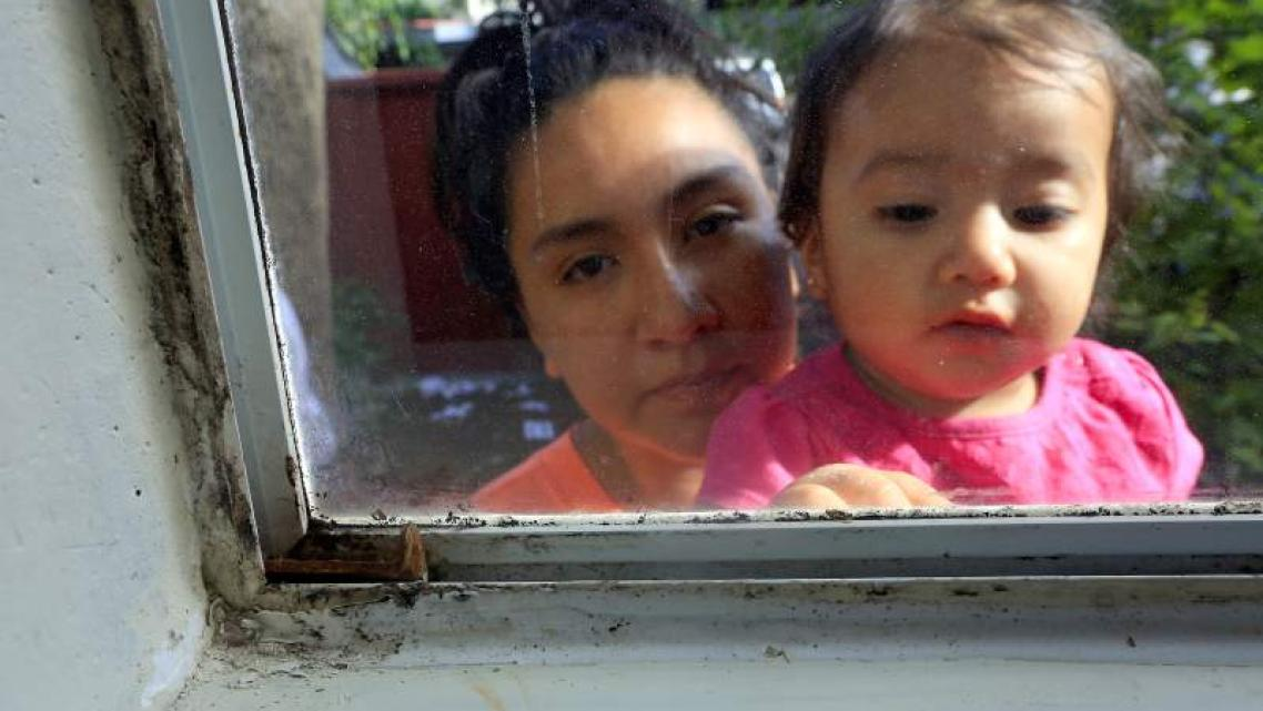 Guadalupe Vargas with her daughter Jaylani, 1, outside their mold covered bedroom window at the Walnut Creek Apartments.
