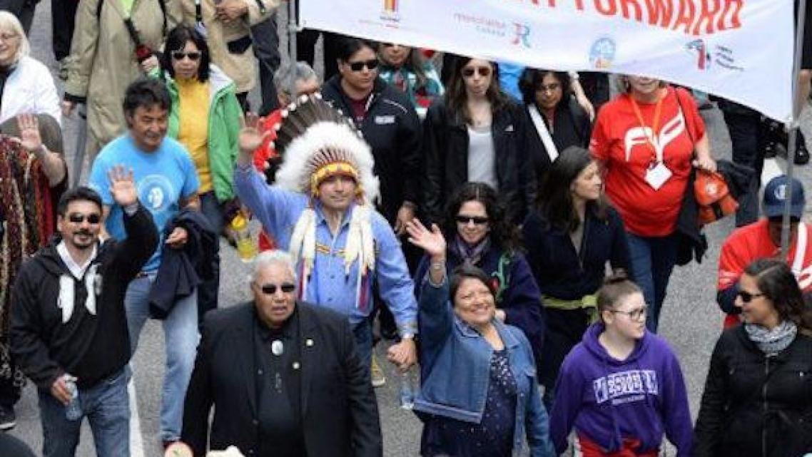 JUSTIN TANG/THE CANADIAN PRESS Truth and Reconciliation commissioner Murray Sinclair, in a black suit, marches along with Assembly of First Nations Chief Perry Bellegarde (in headdress) in an Ottawa march on Sunday that was part of the closing events of the commission's work. Between 7,000 and 10,000 participants marched.