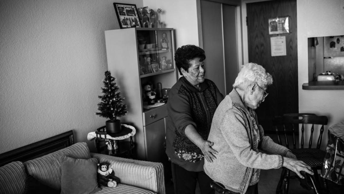Maria Martínez helps her client, Agripina Castellanos, as she walks inside her Angelus Plaza apartment. (Photo by Bear Guerra)