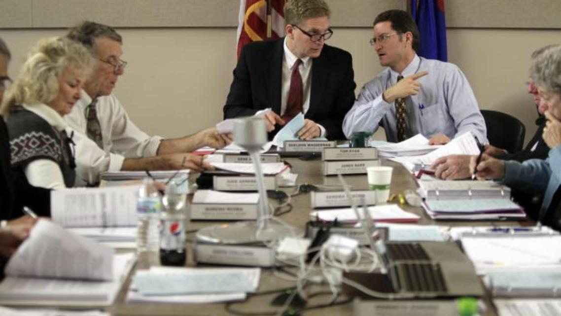 Dr. Sheldon Wasserman, center, chairman of the Wisconsin Medical Examining Board, talks with Tom Ryan, right, executive director of the board. On the left are board members Jude Genereaux and Dr. Gene Musser. The 13-member board, appointed by the governor, includes 10 doctors and three public members. M.P. King