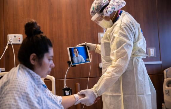 A hospital worker speaks through a remote Spanish translator while preparing a COVID-19 patient take her first steps after being