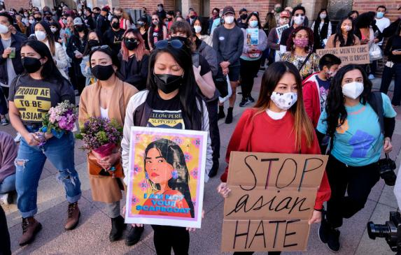 Demonstrators wearing face masks and holding signs take part in a rally to raise awareness of anti-Asian violence