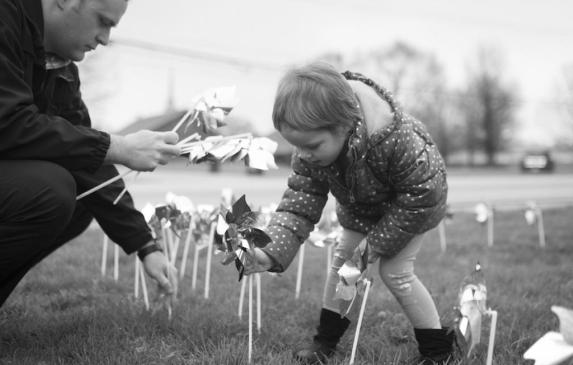 A young girl places pinwheels in the ground with a detective at the Bentonville Police Station at a rally to raise awareness of
