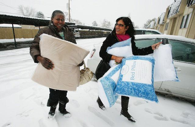 Women of the World founder Samira Harnish, right, delivers bedding to refugee Ngakoutou in Salt Lake City Wednesday, Dec. 11, 2013. Harnish came to America from Iraq in the 1970s.