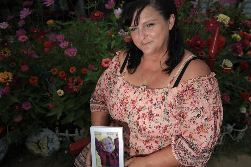 Brenda Wezowicz holds a photo of her granddaughter, Karma Wezowicz, as she sits in front of a buttefly garden she and Karma had planned together and is dedicated to Karma. Karma was accidentally shot in late February 2017 and died a few days later.