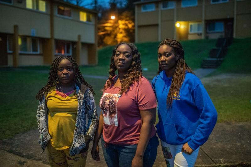 """Kisha Simms, 38, center, poses with her daughters Deitra """"DeeDee"""" Jackson, 11, and Lynaya """"Naya"""" Saylor, 18, under the glow of a street light in their neighborhood, Springfield Apartments."""