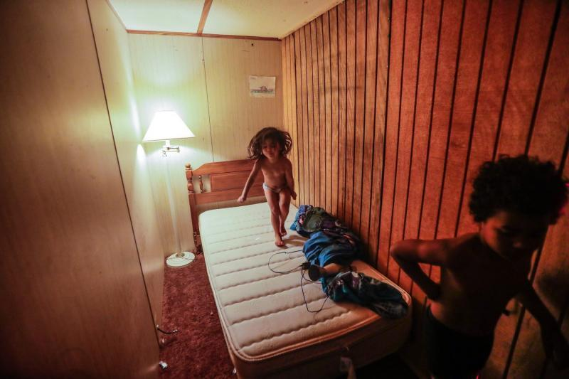 Victoria, 3, bounces on a twin bed in a room by a wall built to create an extra bedroom in her family's trailer. Her 8-year-old Romeo walks through the room.