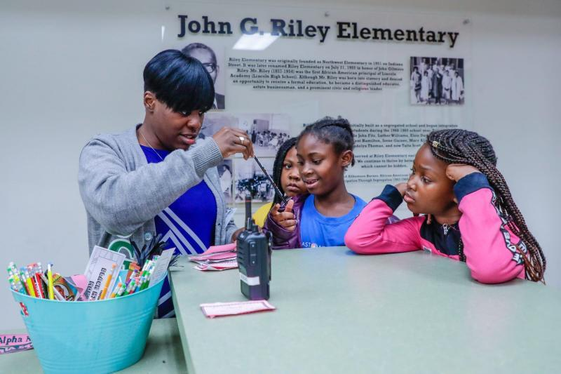 Riley Elementary School Principal April Knight hands out pencils and bookmarks to students who answered the daily Black History Month trivia question correctly.