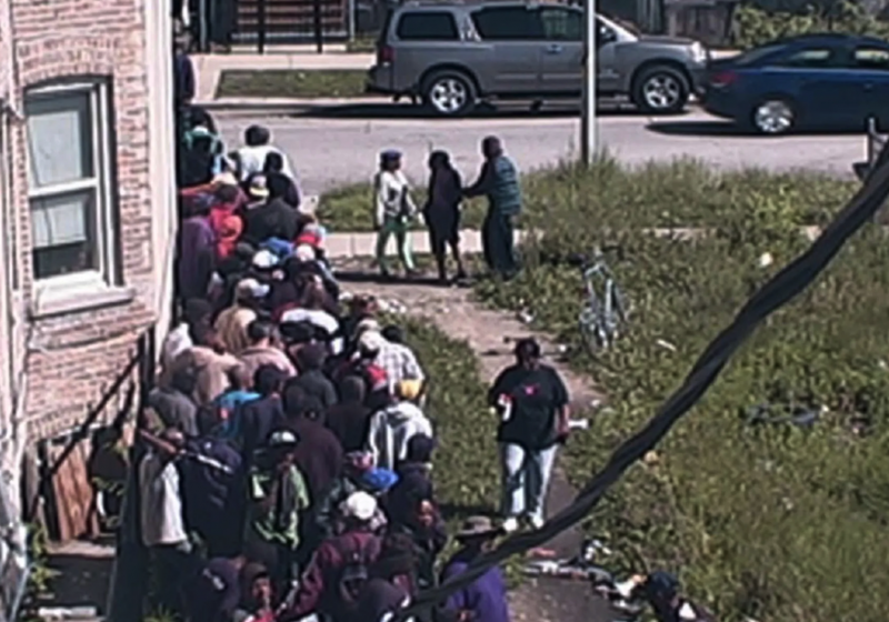 People line up to buy from a heroin market on Chicago's West Grenshaw Street in 2015. The photo was introduced in a federal criminal complaint against an alleged drug dealer. (Credit: Photo via federal complaint)