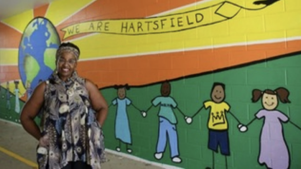 Dr. Rhonda Flanagan-Blackwell standing near a bright, rainbow mural painted on the halls of her school