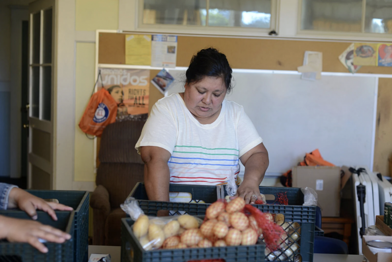Diana Gomez Martinez sorts food donations for deliveries on June 23 2021.