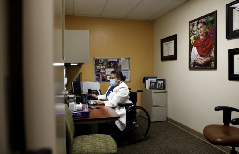 """Dr. Marie Flores, working at her desk at AltaMed, says that, for her, """"identifying as a woman is wanting to be a mother. When people judge you and question your ability to do that, it's very, very hurtful."""" (Christina House / Los Angeles Times)"""