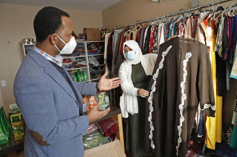 Halima Ismail, right, assists customer Abdirahman Farah, who is shopping for his wife at H.E.A.L Buffalo, a nonprofit that supports refugees' career preparation.