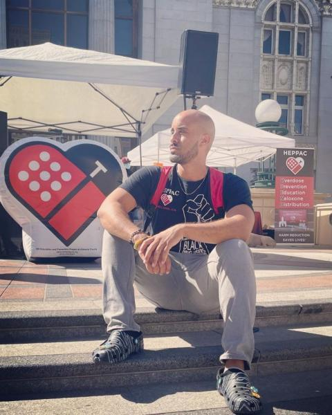 Braunz E. Courtney sits on the steps of Oakland's Oscar Grant Plaza on August 31—HEPPAC set up a booth to commemorate International Overdose Awareness Day, giving out free food and hosting Narcan trainings. (Courtesy of HEPPAC)