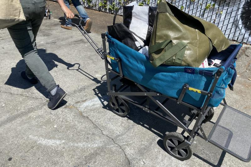 An outreach worker with Punks With Lunch pulls a handcart with sterile supplies in West Oakland / Ariel Boone