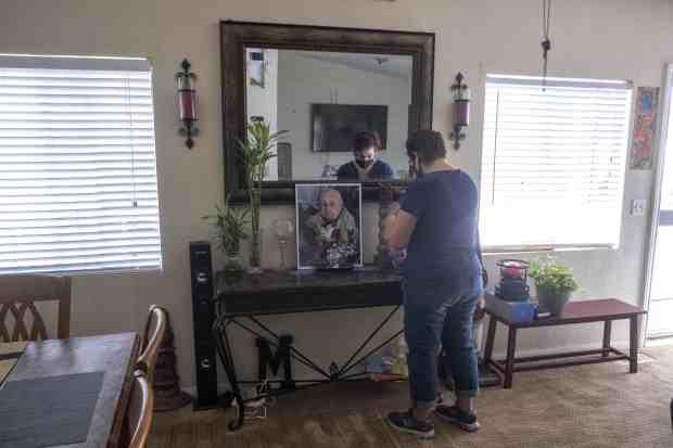 Marisela Munoz looks at a photo of her aunt, Evangelina C. Martinez, who raised her since birth, at her home in Canyon Country, Friday Aug. 28, 2020. Martinez, a resident of Astoria Nursing and Rehabilitation Center in Sylmar, died after becoming ill with COVID-19 at the age of 93. (Photo by Hans Gutknecht, Los Angeles Daily News/SCNG)
