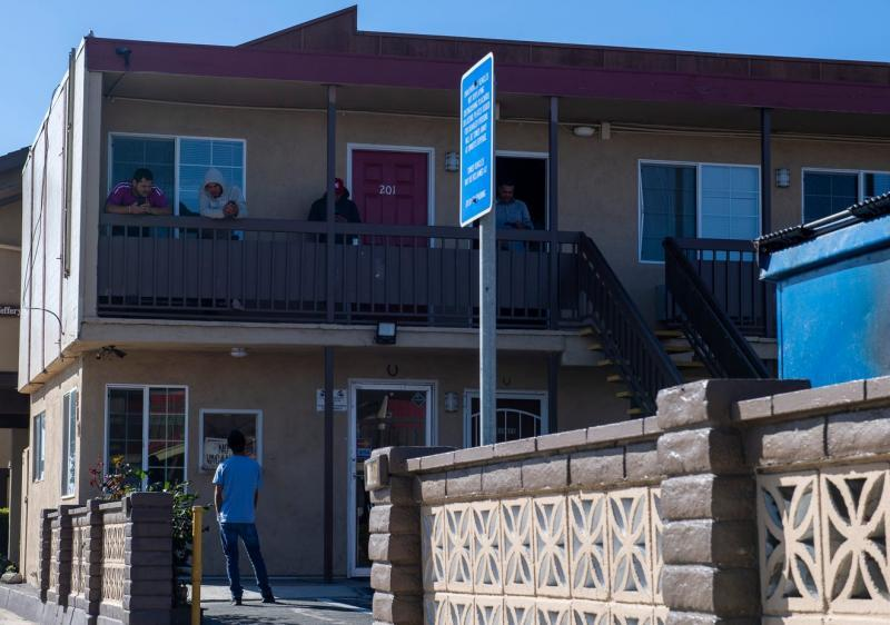 A few H2A workers hanging out on the second floor of the Budget Inn Motel in Salinas talk to a person standing just right outside their room on April 2, 2020. David Rodriguez/The Salinas Californian