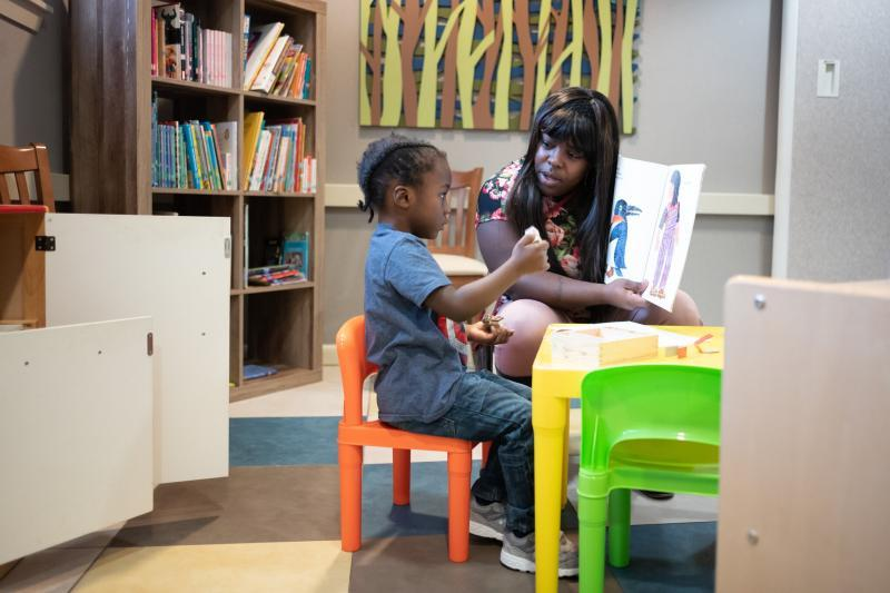 Ms. Jones reading to her son Christopher Michael in the community room of their apartment building.Credit...Cheriss May for The New York Times