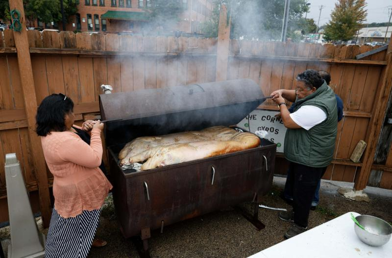 Before coronavirus arrived, Irene Maun Sigrah, a health worker focused on the care of Pacific Islanders living in America, left, assists Maitha Jolet during an annual community hog roast October 5, 2019 in Dubuque, Iowa. | M. Scott Mahaskey / POLITICO