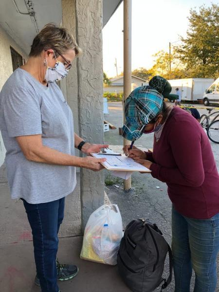 Ruth DeYoe of Mision Peniel in Immokalee requests the signature of a farmworker who is receiving financial help from the social services organizatioon in January 2021 after the woman's son tested positive for the coronavirus and she was unable to work. Janine Zeitlin/USA Today Network Florida