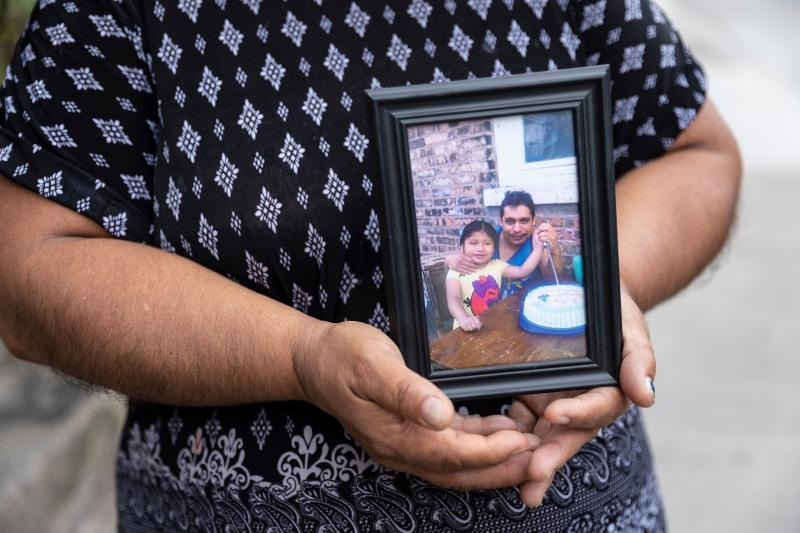Candelaria Lucero holds an old photo of her husband Margarito and daughter Isamari. Margarito died of COVID-19 in May. Manuel Martinez / WBEZ