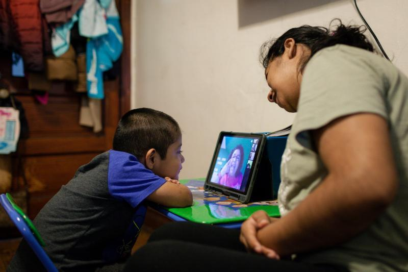 Sarai Camarillo supports her 4-year-old son, Isaac Ayala, for his daily hour of remote learning. Camarillo quit her job at a bakery so she could help her kids as they learn from home. Michelle Kanaar / WBEZ