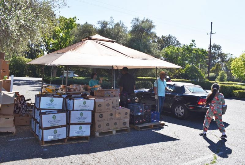 Volunteers help load boxes of food into vehicles after asking drivers how many boxes of food they want on June 4, 2021, at a food distribution site in Palo Alto. Photo by Kate Bradshaw.