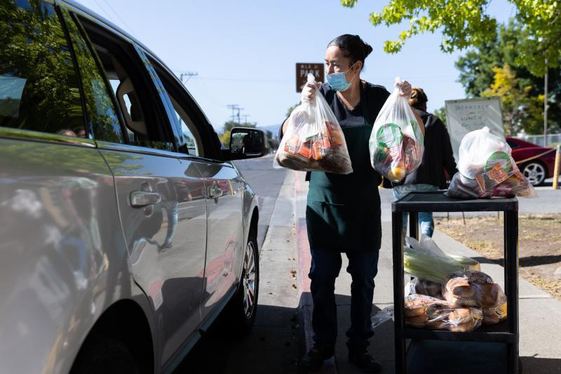 Norma Lazcano lifts bags of food into a client's car at a food pick-up site at the Los Robles Ronald McNair Academy in East Palo Alto on May 19, 2021. Photo by Magali Gauthier.