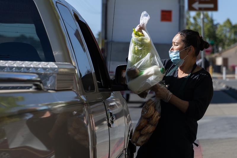 Norma Lazcano places bags of food in a client's car at a food pick-up site at the Los Robles Ronald McNair Academy in East Palo Alto on May 19, 2021. Photo by Magali Gauthier.