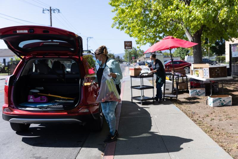 Irma Muñoz places bags of food in a client's car at a food pick-up site at the Los Robles Ronald McNair Academy in East Palo Alto on May 19, 2021. Photo by Magali Gauthier.