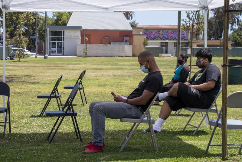 Freshly vaccinated individuals sit for about 15 minutes after receiving a one-dose during a mobile vaccine clinic at the rear of MacArthur Park in Central Long Beach on Tuesday, May 25, 2021. Photo by Crystal Niebla.