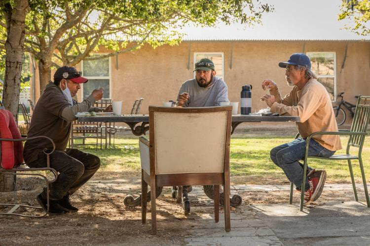 Jose Segura, left, eats dinner with his fellow River Ranch residents. Neither Segura nor his wife or daughter have health insurance because the employer-offered and private-payer premiums are too costly for them to afford, Segura said, but he and his wife make too much annually to qualify for MediCal.  Clark James Mishler