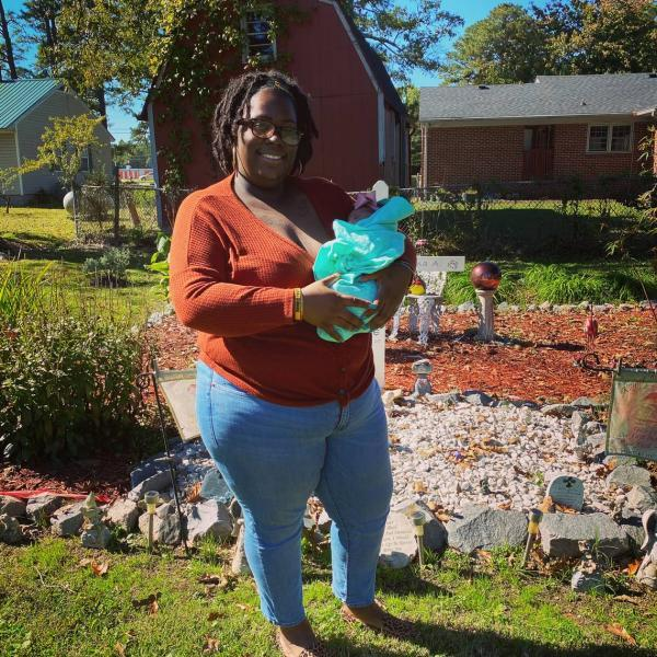 Renee Schoolfield stands with her infant daughter born in September 2020, Azlyn Briel, in front of the burial site for her two children who died after being born prematurely. CONTRIBUTED