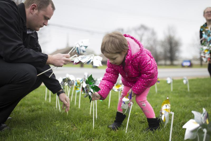 Elizabeth Crouch, 4, (center) places pinwheels in the ground with Det. Adam Corbett (left), at the Bentonville Police Station at a Cherishing Children rally in April 2018 to recognize child abuse investigators and promote prevention of child maltreatment. The pinwheels represented each confirmed case of child abuse and served as a reminder of a child's innocence. Doves released at the rally recognized children who had died of abuse.