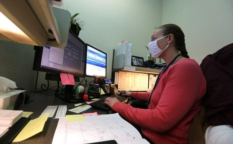 Child abuse hotline operator Amanda Whitlock works on abuse reports at her workstation on Jan. 27 at the Arkansas State Police headquarters in Little Rock.