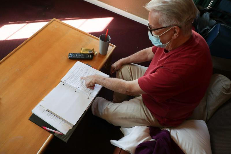 Lee Fournier sorts through a binder with potential housing options in his hotel room provided by Project Roomkey on Sunday, October 11, 2020, at Rodeway Inn & Suites in Indio, Calif. Project Roomkey is an effort by the state to house individuals experiencing homelessness during the COVID-19 pandemic. VICKIE CONNOR/THE DESERT SUN