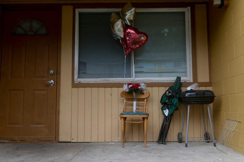 Balloons, a single candle and a bouquet of plastic flowers are placed on a front porch in the building. TORI SCHNEIDER/TALLAHASSEE DEMOCRAT