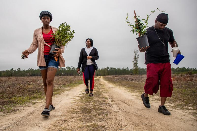 "Koquisha Cook, 35, left, and her boyfriend Kevin Moore carry plants as they walk to Noonie's gravesite. Jamirica ""Noonie"" Cook, 15, was shot and killed last year in her home at Springfield Apartments. Noonie's sister Sharail ""Sugar"" Sampson, 14, carries a heart-shaped box of chocolates to leave on her sister's grave. ALICIA DEVINE/TALLAHASSEE DEMOCRAT"