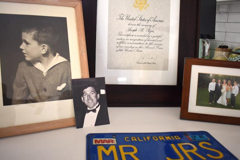 Family photos of Joseph Richard Sizoo II, as well as his recognition from President Joe Biden for his naval service and his vintage California license plate with his JRS initials. The license plate had been in his room at Channel Islands Post Acute. (Brooke Holland / Noozhawk photo)