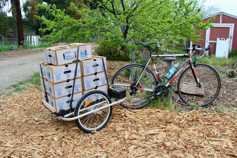 A bicycle with a trailer affixed to the back is loaded with food boxes to deliver during a Saturday morning session of the Eastside Connect program led by Veggielution and the Silicon Valley Bicycle Coalition on April 3, 2021. Courtesy Silicon Valley Bicycle Coalition.