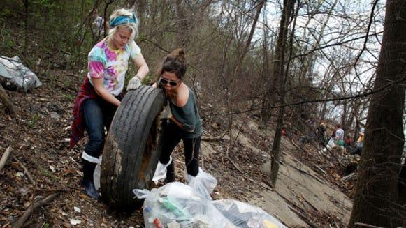 Ilsa Dewald, 19, and Chelsea Krist, 21, both from the University of Iowa, are among about 50 students cleaning up McKellar Lake through Living Lands & Waters' Alternative Spring Break. Last year the group collected 160,000 pounds of garbage from McKellar Lake in 12 days.