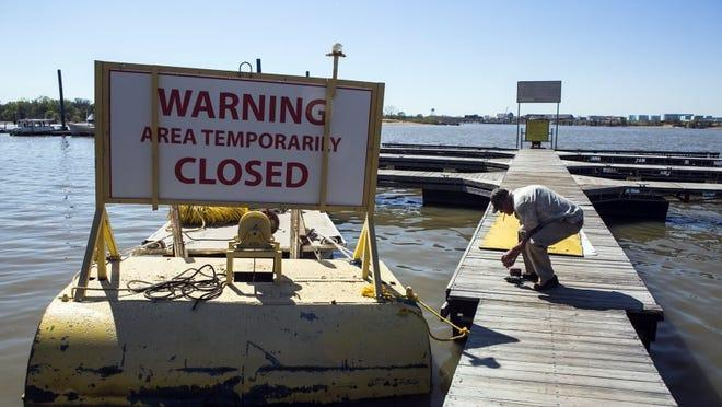 April 4, 2016 - Larry Stanley, owner of Riverside Lake Marina, picks up tools from his dock after a warning sign was installed on one of his work boats at McKellar Lake Monday. The City of Memphis has closed the boat ramp at 1875 McKellar Drive, which allows access to McKellar Lake, after a major sewer line transporting wastewater to the TE Maxson Wastewater Treatment Plant that was damaged. (Yalonda M. James/The Commercial Appeal)