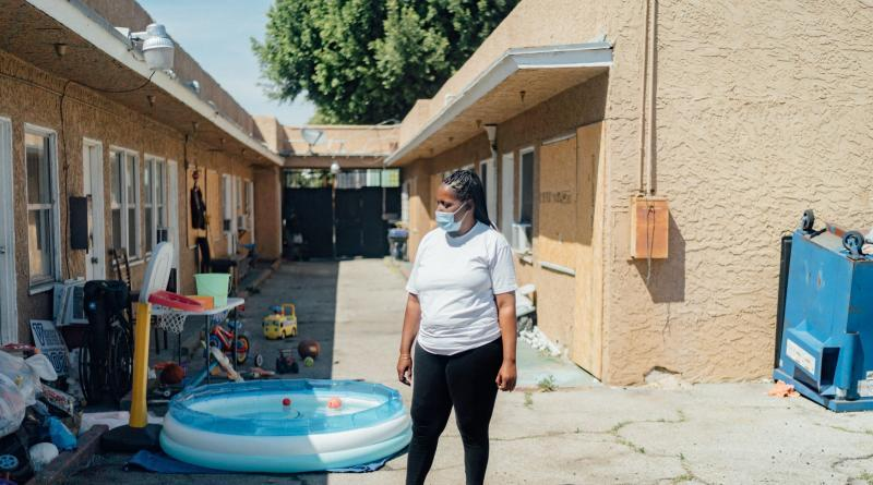 Kim Moore stands in a courtyard of the unpermitted apartment complex where she lives in L.A.'s Mid-City neighborhood. (AL KAMALIZAD/LAIST)