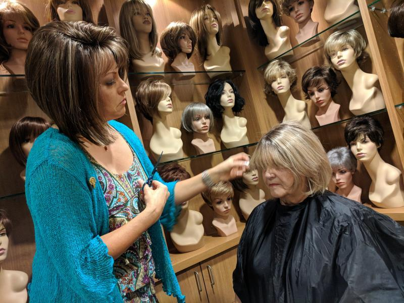 Lemonade Locks wig boutique owner Kelly Giblin fits a hairpiece onto retired Kern County Deputy Sheriff Brenda Blanton, who suffered from hair loss associated with the valley fever medication fluconazole. (Photo by Kerry Klein/KVPR)