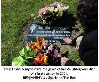 Thuy Thanh Nguyen visits the grave of her daughter, who died of a brain tumor in 2001. BENJAMIN VU / Special to The Bee