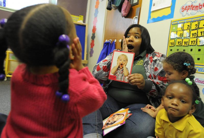 Flashcards with various facial expressions are used to teach children to recognize emotions. Laila Moore, 2 (left,) follows the lead of teacher Michelle Fleming at Little Flowers. They were sitting with fellow two-year olds Kacee Sanford (right front) and Aya Kheribot. (Lloyd Fox/Baltimore Sun)
